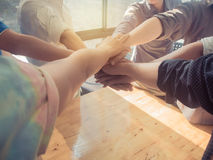 Group of people putting their hands working together on wooden b royalty free stock photo