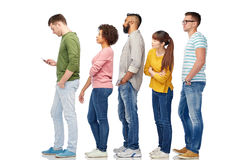 Group of people in queue with smartphone. Technology, ethnicity and people concept - international group of men and women in queue line with smartphone over Royalty Free Stock Image