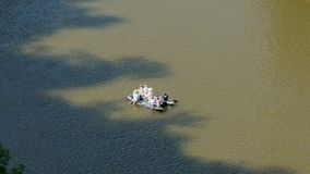 A group of people rafts along the river stock footage