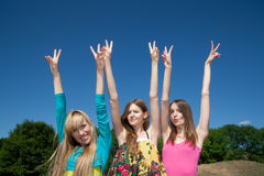 Group of people raise hands in air across blue sky royalty free stock photo