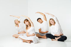 Group of people relaxing and doing yoga in white Royalty Free Stock Photography