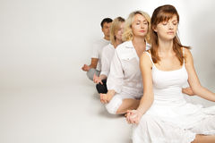 Group of people relaxing and doing yoga in white Stock Images