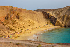 Group of people relaxing on Papagayo beach on the island of Lanzarote, Spain Royalty Free Stock Photos