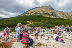 group of people resting after a hike in Five lakes valley in High Tatra Mountains, P Royalty Free Stock Photo