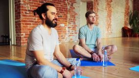 Group of people resting on yoga mats in gym stock video footage