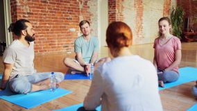 Group of people resting on yoga mats in gym stock footage
