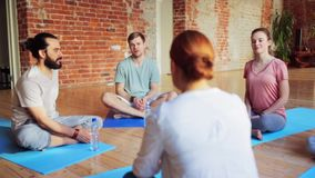 Group of people resting on yoga mats in gym stock video