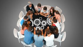 A group of people in a round table and gears. Digital composite of a diverse group of people seated in a round table looking a gears moving stock video
