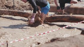 A group of people running through mud pit in obstacle endurance race stock video footage