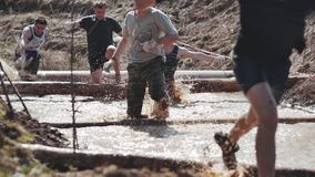 A group of people running through mud pit in obstacle endurance race stock video