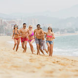 Group of people running at sea beach Stock Photo
