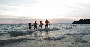 Group Of People Running From Sea At Sunset, Happy Young Friends Together On Beach During Summer Vacation stock footage