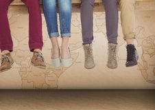 Group of people`s legs sitting on wooden plank in front of world map. Digital composite of Group of people`s legs sitting on wooden plank in front of world map royalty free stock photos