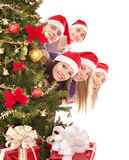 Group  people in santa hat by christmas tree. Royalty Free Stock Photo