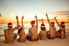 Group of people with Santa hats sitting on sandy beach Royalty Free Stock Image
