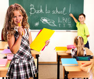Group people schoolchild in classroom. Girl with pens on foreground. Royalty Free Stock Images