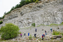 Group of people searching for ammonite fossils in limestone. Royalty Free Stock Photos