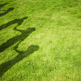Group people shadow on green grass royalty free stock photography