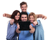 Group of people showing  screen of  tablet and point fingers Royalty Free Stock Image