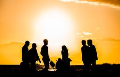 A group of people silhouette walking at the seaside at sunset in Izmir, Turkey. A group of people silhouette walking at the seaside at sunset in Alsancak, Izmir royalty free stock images