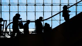 Group of people silhouettes moving on escalator. Traffic of society and population to depart or meeting in public place or mall slowmotion. Social symbol of stock video footage