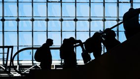 Group of people silhouettes moving on escalator. Traffic of society and population to depart or meeting in public place or store slowmotion. Social symbol of stock footage