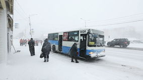 Group of people sit in public city bus during snowfall snowstorm stock video