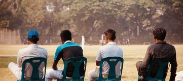Group of people sitting around a place. A group of people sitting on plastic chairs watching the game together unique photo royalty free stock photos