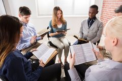 Group Of People Reading Bibles. Group Of People Sitting On Chair In Circle Reading Bibles stock photography