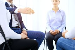 Group of people sitting in a circle during therapy. Meeting of business team participating in training.  stock photo