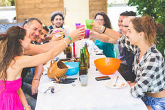 Group of people sitting having lunch together and toasting Stock Images