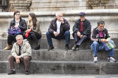 Group people sitting on marble steps, Catania, Sicily. Italy Stock Photo