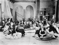 Group of people sitting on oversized cushions in a hall Royalty Free Stock Images
