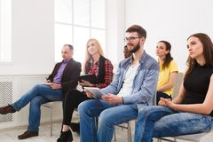 Group of people sitting at seminar, copy space. Interested and laughing audience listening to speaker. Education, conference, workshop concept stock photography