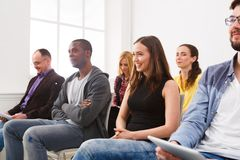 Group of people sitting at seminar, copy space. Interested and laughing audience listening to speaker. Education, conference, workshop concept Stock Image