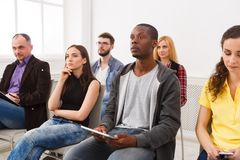 Group of people sitting at seminar, copy space. Serious and concentrated audience listening to speaker. Education, conference, workshop concept Stock Photo