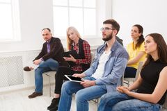 Group of people sitting at seminar, copy space. Serious and concentrated audience listening to speaker. Education, conference, workshop concept stock photography