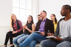 Group of people sitting at seminar, copy space. Interested and laughing audience listening to speaker. Education, conference, workshop concept stock photos