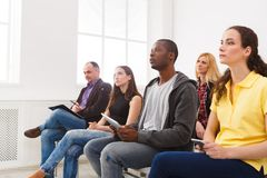 Group of people sitting at seminar, copy space. Serious and concentrated audience listening to speaker. Education, conference, workshop concept Stock Images