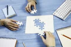Finally finding solution. Group of people sitting at table and assembling jigsaw puzzle Stock Image