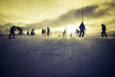 Skiing in the golden hour. Group of people skiing at sunset stock photography