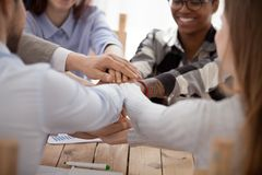 Group of people stacking hands sitting in office together stock images