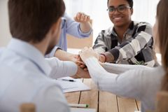 Group of people stacking hands sitting in office together stock photos