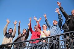 Group of people stand with hands lifted in greet stock photos
