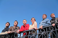 Group of people stand leaning on handrail stock images