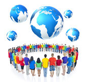 Group of People Standing around the Globe stock photo