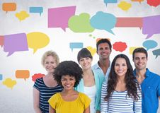 Group of people standing in front of colorful chat bubbles Royalty Free Stock Photography