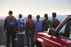 Group of people standing next to the car and looking at the mountains Stock Photo
