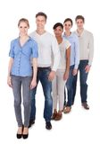 Group of people standing in a row. Happy Group Of People Standing In A Row Over White Background stock photo