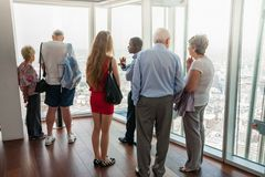 Group of people standing on an upper level floor of high-rise building talking with outlook to city view below royalty free stock photos